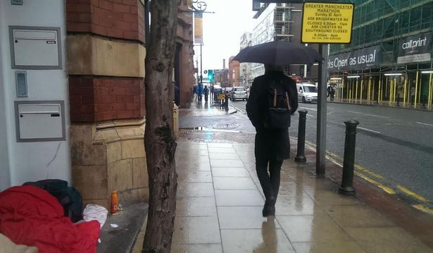 A commuter passes a rough sleeper on Deansgate