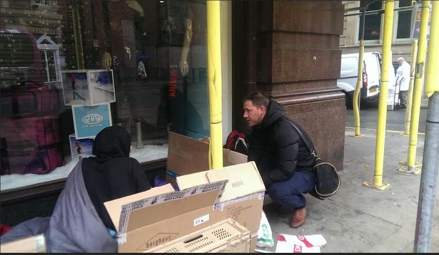 A council homelessness worker talks to a rough sleeper on Deansgate