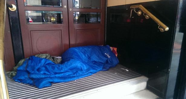 A rough sleeper in the doorway of the Palace Theatre