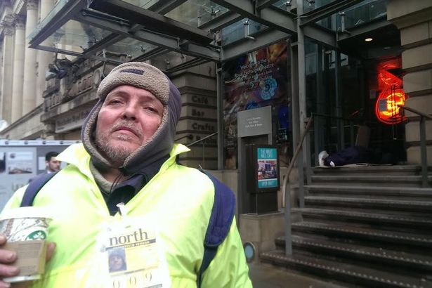 Former rough sleeper-turned Big Issue seller Kevin stands in front of the Royal Exchange